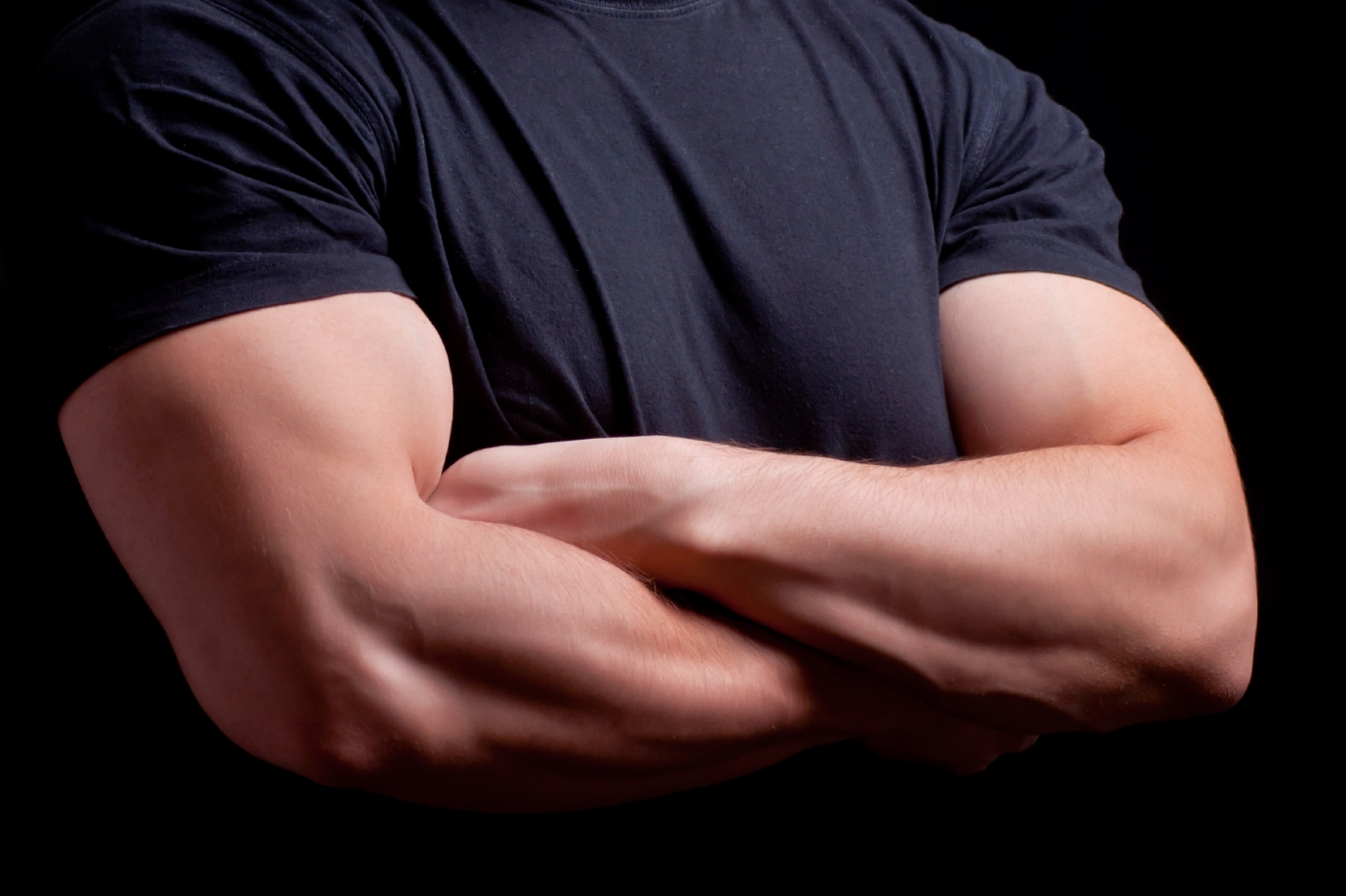 Male security guard with strong arms crossed in a dark background